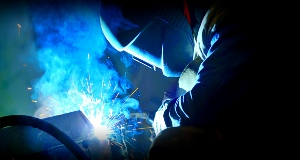 Man wearing a welding mask welding a peice of equipment.